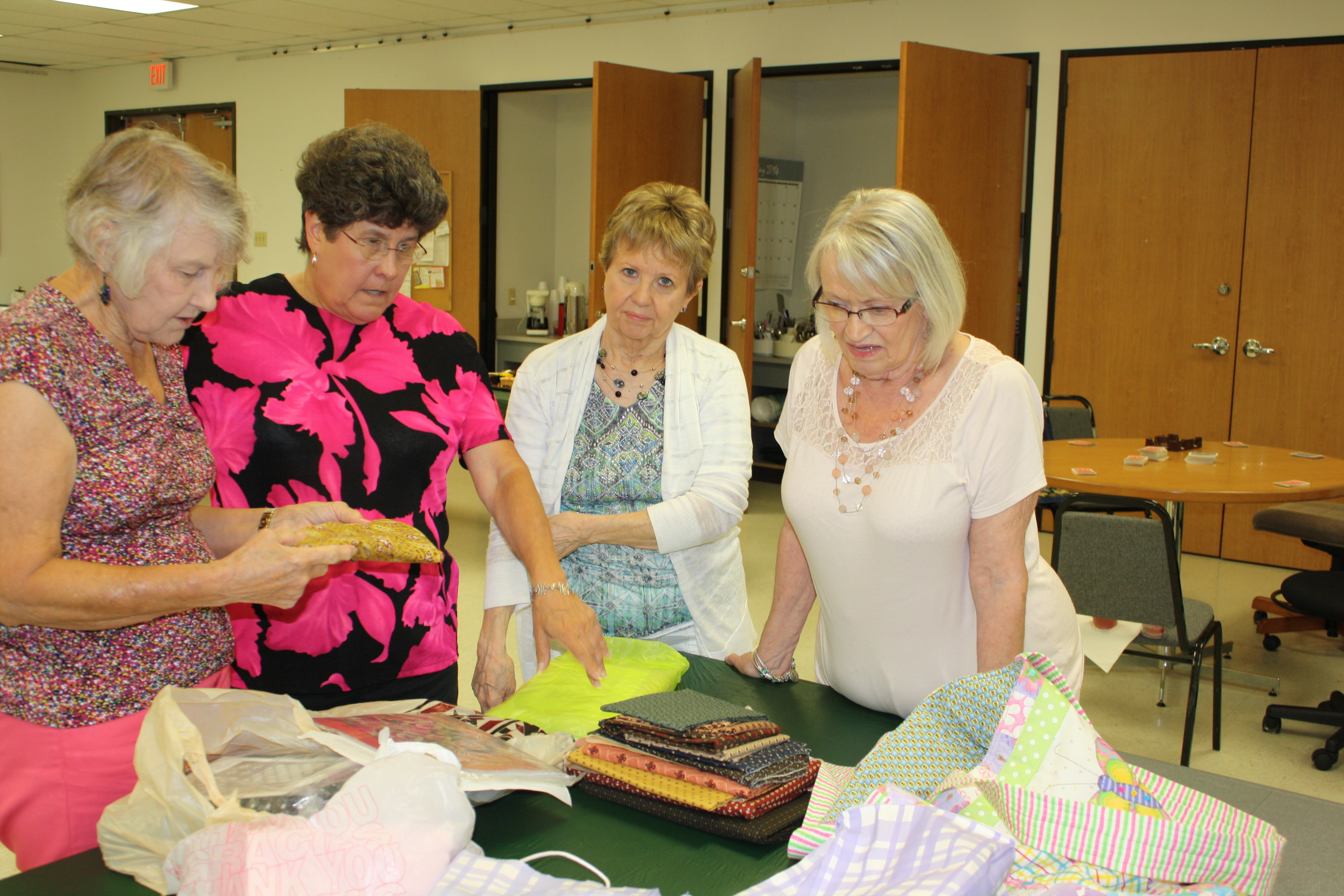 Four women looking at quilt supplies